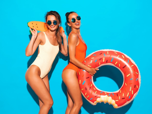 Two beautiful sexy smiling women in summer colorful swimwear bathing suits. girls in sunglasses. positive models having fun with colorful penny skateboard. with donut lilo inflatable mattress Free Photo
