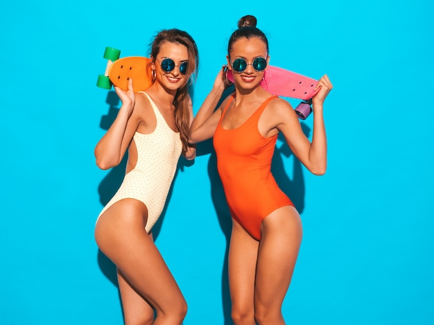 Two beautiful sexy smiling women in summer colorful swimwear bathing suits. trendy girls in sunglasses. positive models having fun with colorful penny skateboards. isolated Free Photo