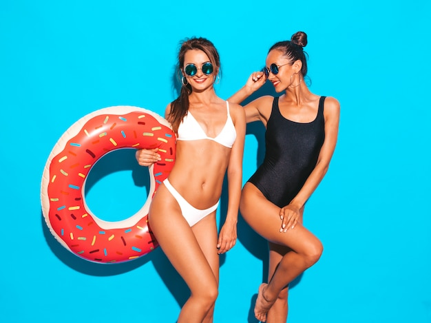 Two beautiful sexy smiling women in summer white and black swimwear bathing suits.girls in sunglasses. positive models having fun with donut lilo inflatable mattress.isolated on blue wall Free Photo