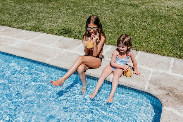 Two beautiful sister kids at the pool drinking healthy orange juice and having fun outdoors. summertime and lifestyle concept Premium Photo