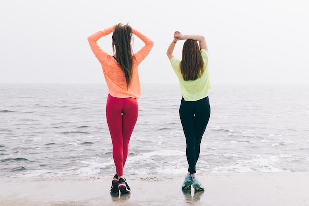 Two beautiful slender young girls are engaged in gymnastics on the beach Premium Photo