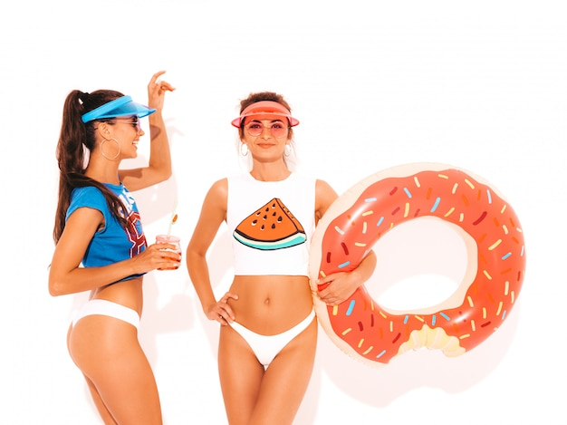 Two beautiful smiling sexy women in white summer underpants and topic. girls in sunglasses,transparent visor cap. models drinking fresh cocktail smoozy drink with donut lilo inflatable mattress Free Photo