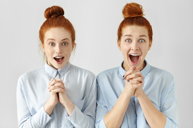 同じシャツに身を包んだ2つの美しいびっくりした生姜髪の女性労働者 無料写真