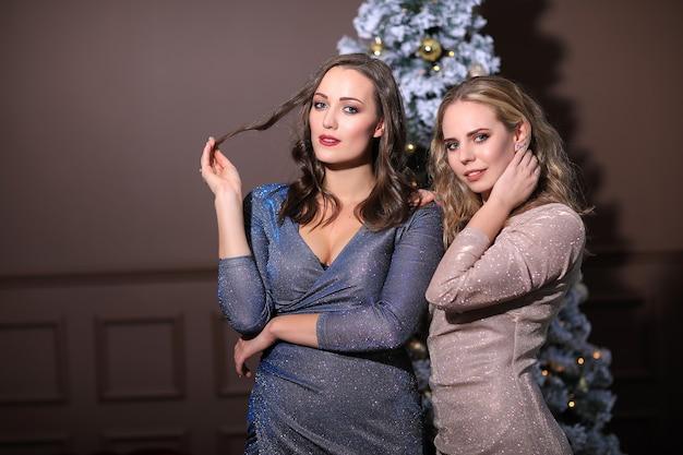 패션 드레스와 함께 크리스마스를 축 하하는 두 아름 다운 여자. 집에서 크리스마스 무료 사진