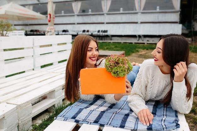 Due belle donne giacciono sulla panchina e si scambiano dei regali Foto Gratuite