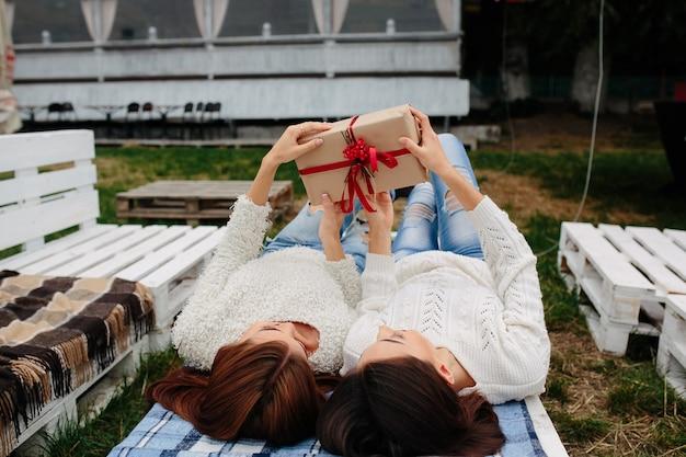Due belle donne giacciono sulla panchina e disimballano un regalo Foto Gratuite