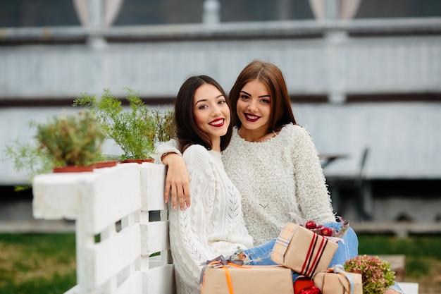 Due belle donne sedute su una panchina, tenendo in mano i regali e guardando Foto Gratuite