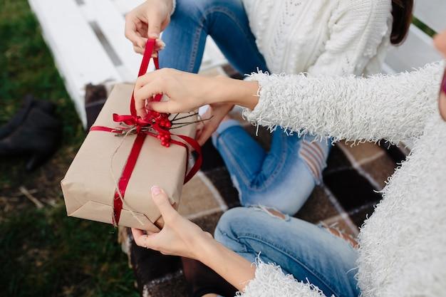 Due belle donne sedute su una panchina e tenendo in mano i regali, vista ravvicinata Foto Gratuite