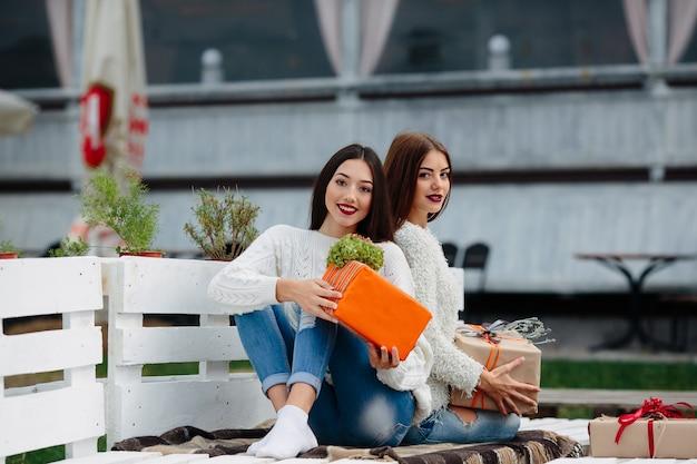 Due belle donne sedute su una panchina e che tengono in mano i regali Foto Gratuite