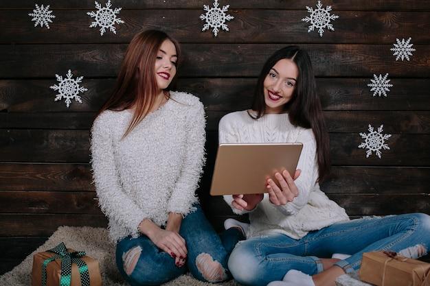 Due belle donne sedute per terra con una tavoletta, tra i regali di natale Foto Gratuite