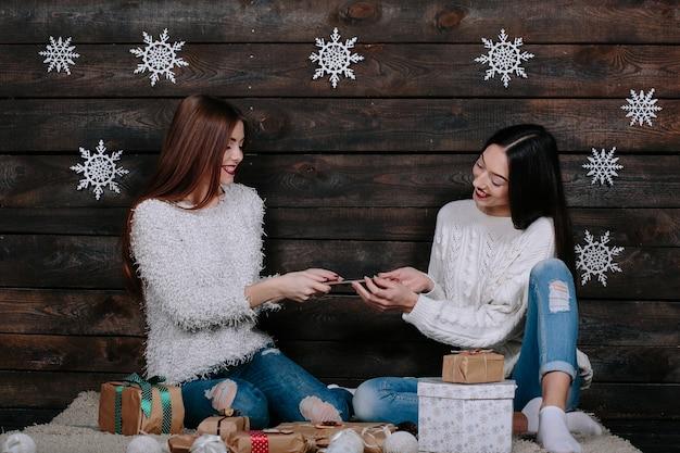 クリスマスのギフトの間に、タブレットで床に座っている2人の美しい女性 無料写真