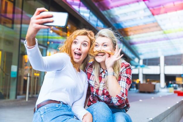 Two beautiful women taking a funny selfie Premium Photo