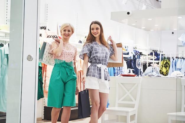 衣料品店を歩きながら笑顔でお互いを見つめるバッグを持つ2人の美しい女性 無料写真