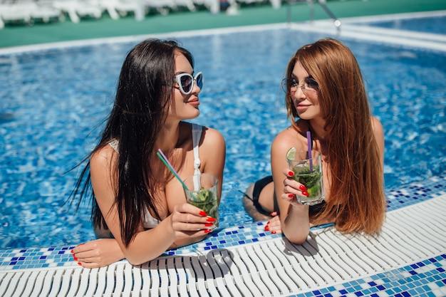 Две красивые женщины с красивыми фигурами в бело-черном купальнике загорают у бассейна и пьют освежающие коктейли. Premium Фотографии