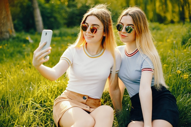 Two beautiful young beautiful girls with shiny blond hair and a skirt and sitiing with phone Free Photo