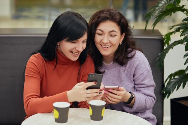 コーヒーを飲みながら携帯電話を見てカフェに座っている2人の美しい若い女性、幸せそうに見えて、一緒に時間を過ごすことを楽しんでいる、肯定的な表情の女性。 無料写真