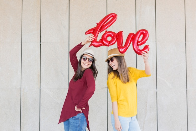 Two beautiful young women having fun outdoors with a red balloon with a love word shape. casual clothing. they are wearing hats and modern sunglasses. lifestyle outdoors Premium Photo
