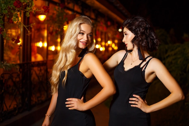 Two beautiful young women posing on camera in the lights of the night city Premium Photo