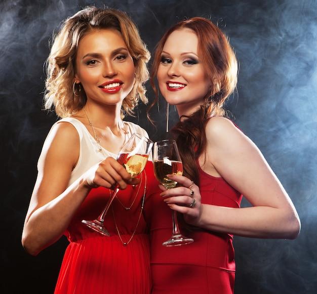 Две красивые молодые женщины с бокалами Premium Фотографии
