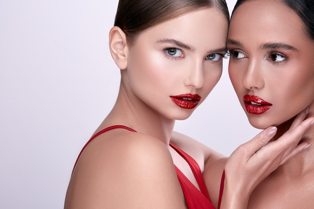 Two beauty faces with red lipstick, handsome women on grey background Premium Photo