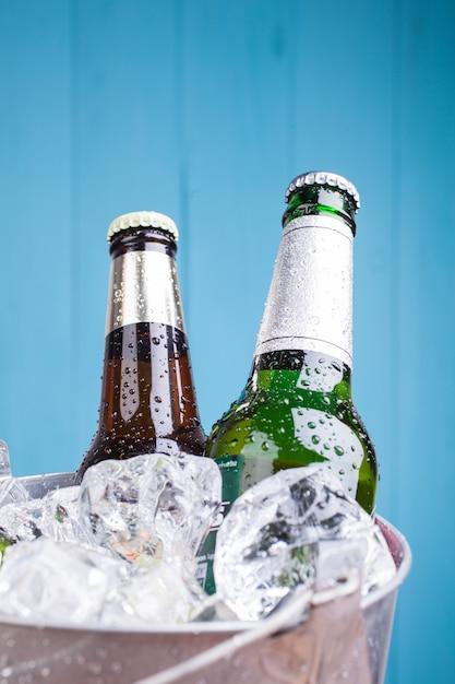 Two beer bottles inside ice bucket Premium Photo