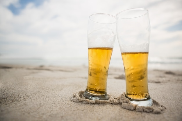 Two beer glasses kept on sand Free Photo