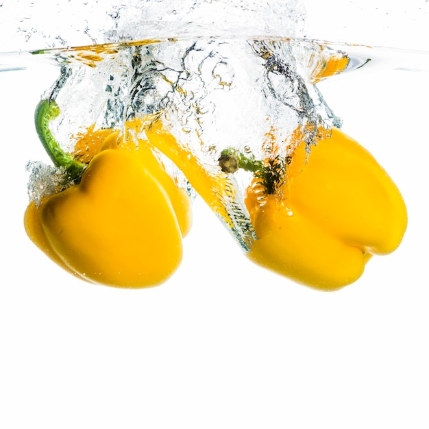 Two bell pepper falling into the water splash on white background Free Photo