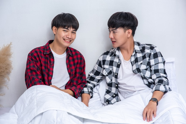Two beloved young men slept in bed together. Free Photo