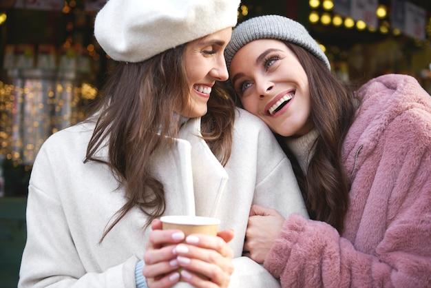 クリスマスマーケットで時間を楽しんでいる2人の親友 無料写真