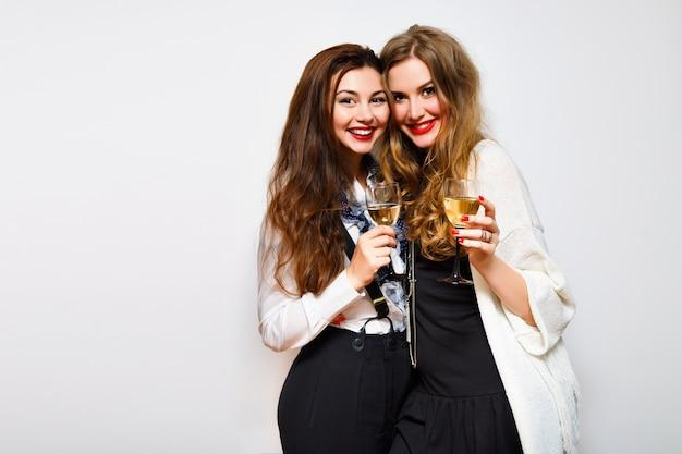 黒と白のパーティーで楽しい2人の親友の女の子、シャンパンの笑顔とゴシップ、誕生日パーティー、エレガントなスタイリッシュな服、白い背景を祝ううれしそうな姉妹を飲む。 無料写真