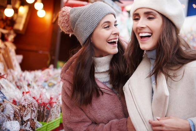 クリスマスマーケットで楽しんでいる2人の親友 無料写真