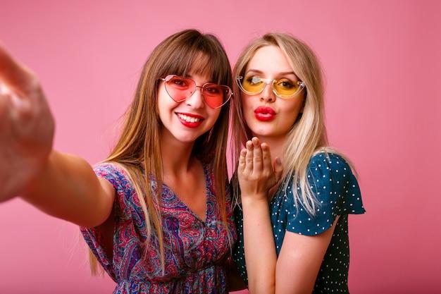 ピンクの壁で自撮りを作る2人の親友の姉妹女性。エアキスを送信し、笑顔、スタイリッシュなドレスとサングラス、春夏気分を送ります。 無料写真