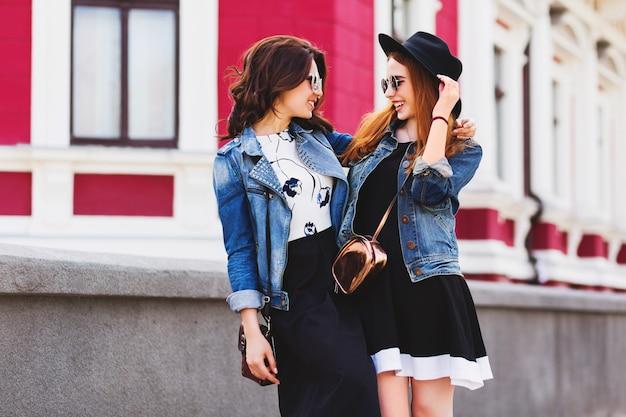 市内中心部の路上で屋外で歩いたり話したりする2人の親友 無料写真