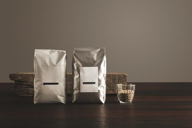 生のサンプルコーヒー豆が入った透明なガラスの近くに空白のラベルが付いた2つの大きな密閉パッケージ 無料写真