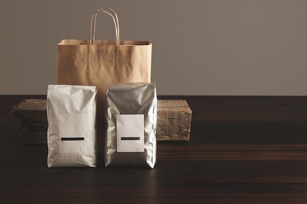 Две большие герметичные упаковки с пустыми этикетками, представленные перед бумажным пакетом и деревенским деревянным кирпичом на красном столе Бесплатные Фотографии