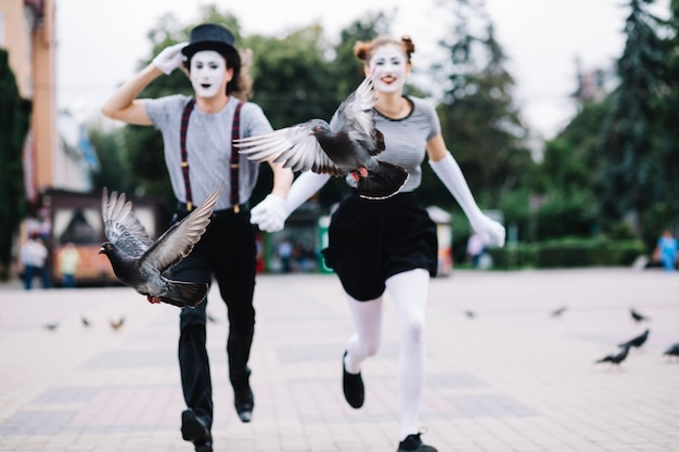 Two birds flying in front of running mime couple on pavement Free Photo