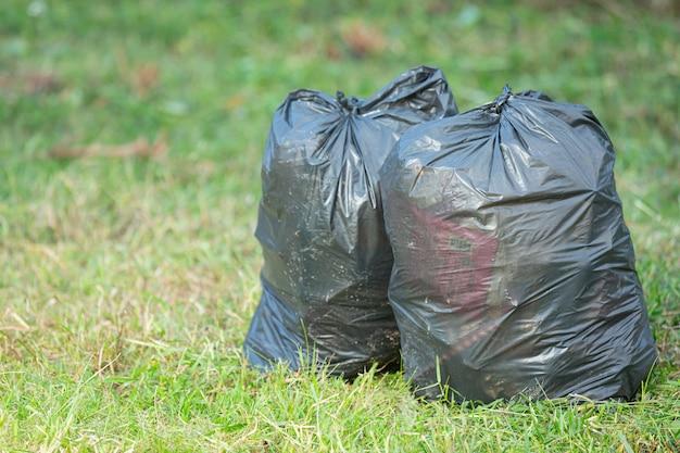 Due sacchi della spazzatura neri messi sul pavimento d'erba Foto Gratuite