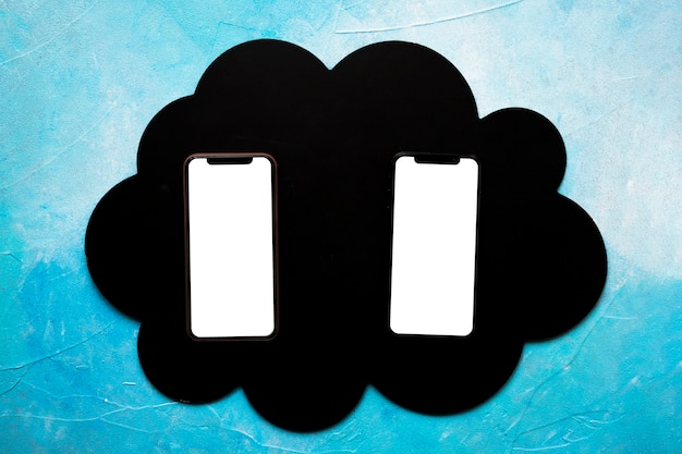 Два пустых мобильного телефона на черном облаке над окрашенной синей стеной Бесплатные Фотографии