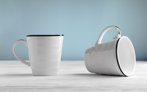 Two blank white mugs on white table and blue background. Premium Photo