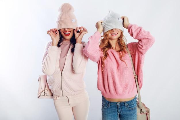흰색 바탕에 스튜디오에서 포즈 핑크 유행 옷에 두 행복 한 여자. 재미, 걷기, 점프, 귀여운 친구 무료 사진