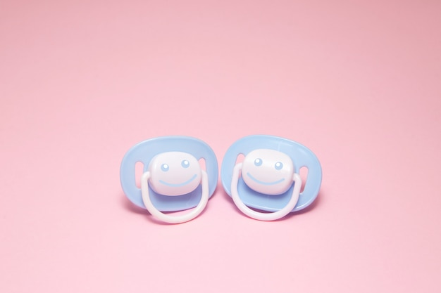 Two blue baby soother or dummy with a smile Premium Photo