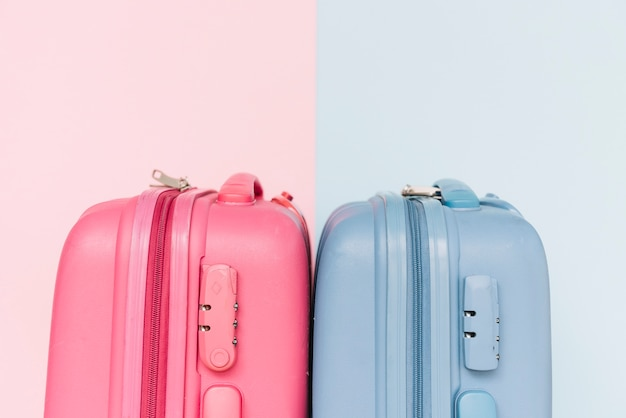 Two blue and pink plastic luggage suitcases on dual background Free Photo