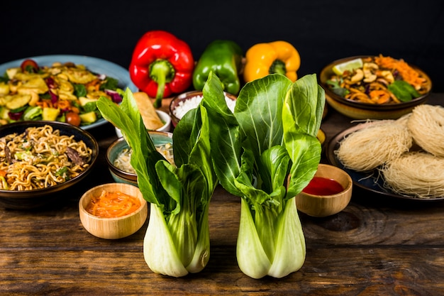 Two bokchoy in front of the thai delicious food on desk Free Photo