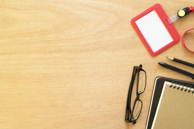 Two books, paperclip, pencil, pen, employee card Premium Photo