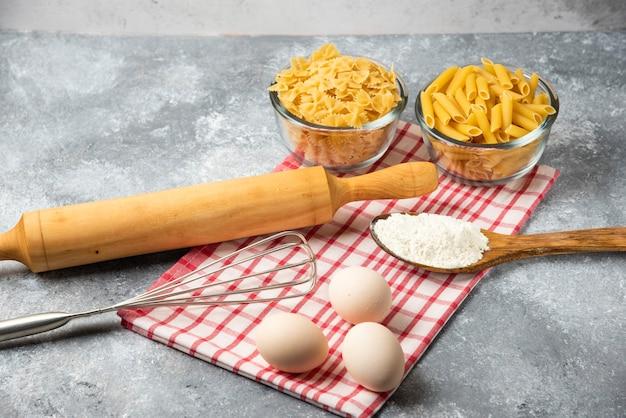 Две миски сырых макарон, яиц, ложки муки и скалки на мраморном столе со скатертью. Бесплатные Фотографии