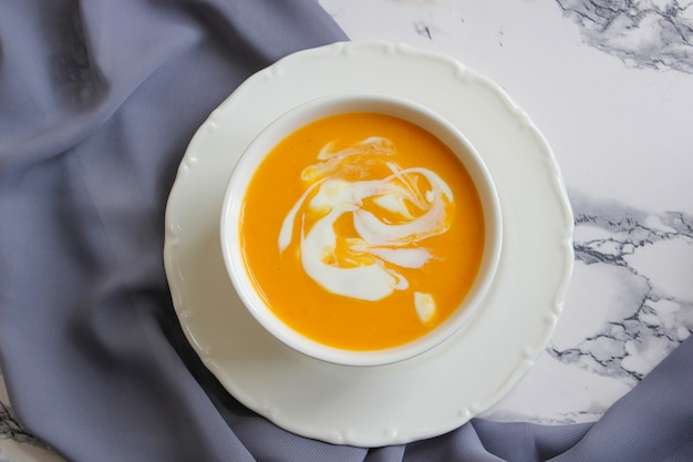 Two bowls of pumpkin soup on white with gray fabric and slices of butternut squash Premium Photo