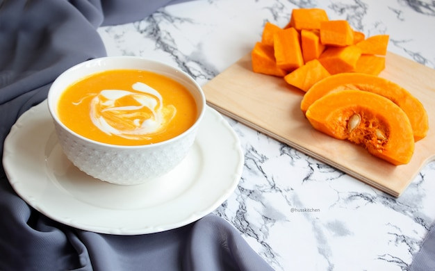 Two bowls of pumpkin soup with gray fabric and slices of butternut squash, top view, vegetarian food Free Photo
