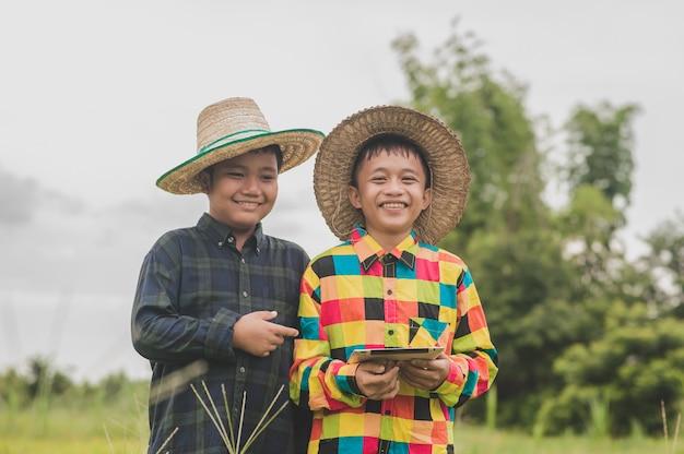 문 농부, 개념 스마트 농부 또는 교육 콜라주 연구 학교 밖으로 서 태블릿을 사용하는 두 소년 아시아 사람 프리미엄 사진