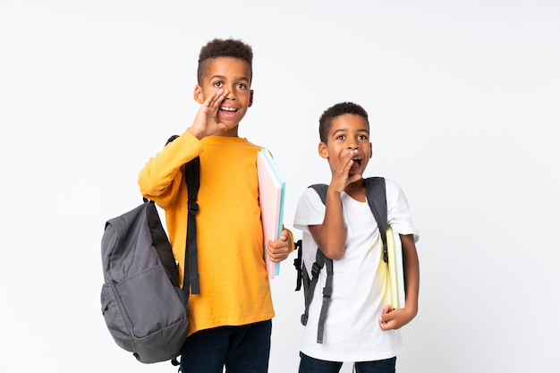 Two boys african american students over isolated white and shouting Premium Photo