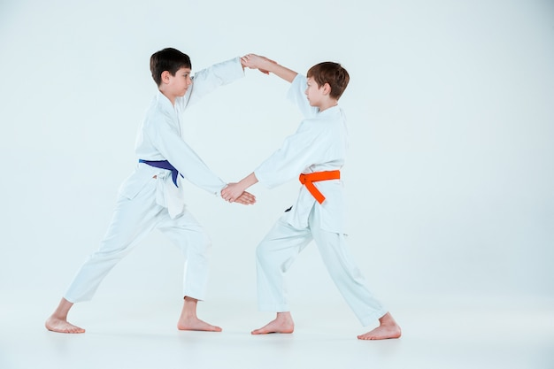 The two boys fighting at aikido training in martial arts school. healthy lifestyle and sports concept Free Photo